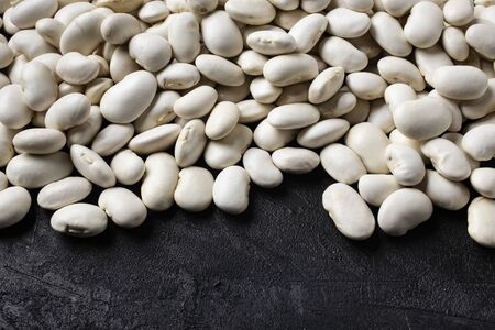 on a textured black background, in the foreground, a pile of dry and raw white beans rich in protein. Zdjęcie Seryjne