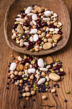 in the foreground, varieties of dried legumes mixed in a large spoon and on a rustic wooden background Zdjęcie Seryjne
