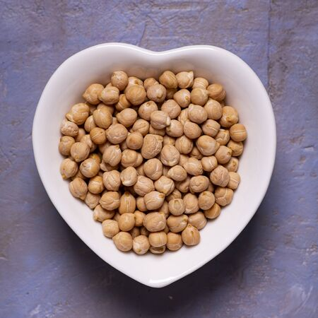 view from top. Dried chickpeas in the foreground in a white ceramic bowl in the shape of a heart on a textured background Zdjęcie Seryjne