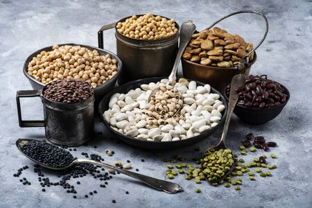 in different rustic metal bowls, on a gray textured background, variety of raw and colorful dry legumes rich in protein