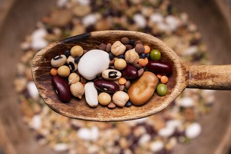 top view, selective focus, in a rustic wooden spoon variety of raw and colorful dried legumes rich in protein