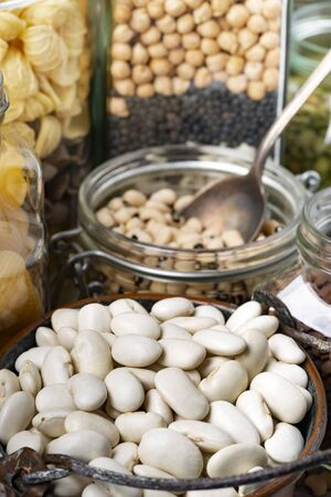 variety of dried legumes and Italian pasta in glass jars in the foreground Zdjęcie Seryjne
