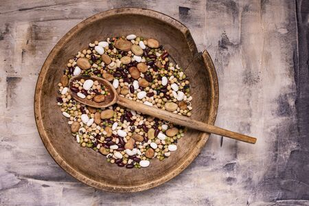 top view, in a rustic wooden plate variety of raw and colorful dry legumes rich in protein Zdjęcie Seryjne