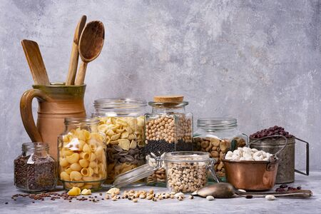 variety of dried legumes and Italian pasta in glass and metal jars. gray background texture. still life Zdjęcie Seryjne