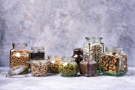 large variety of dried legumes in glass jars. gray background texture