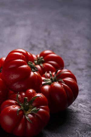 in the foreground, on a textured black background, some ripe and fresh tomatoes covered with drops of water. Copy space