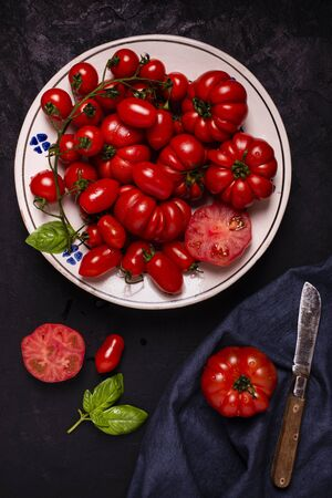 High angle view, on a textured black background, in a rustic dish some varieties of ripe and fresh tomatoes, basil leaves and an old knife. Still life Zdjęcie Seryjne