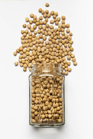 glass jar with dried chickpeas in the foreground, top view, isolated from the white background Zdjęcie Seryjne