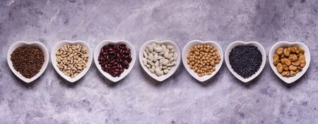 assortment of dried legumes in white ceramic bowls in the shape of a heart arranged in a row with top view on a gray textured background Zdjęcie Seryjne