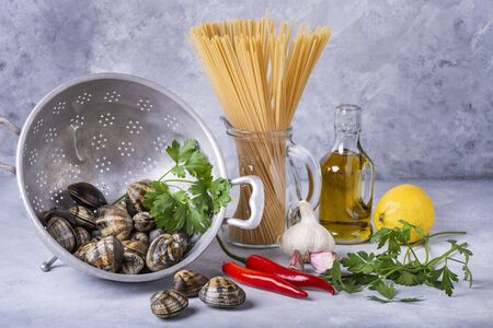 on a gray structure background, in an old colander, fresh clams with shell, spaghetti and various ingredients for the preparation of the pasta. Still life. Zdjęcie Seryjne