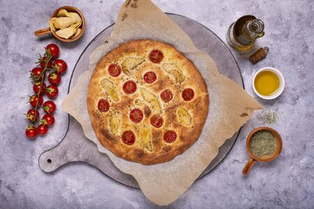 On the wooden cutting board, a rustic and vegetarian flat bread, homemade with cherry tomatoes and artichokes