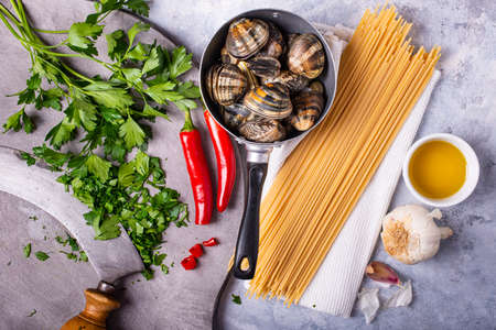 on a gray structure background, in an old colander, fresh clams with shell, spaghetti and various ingredients for the preparation of the pasta. Still life. Stok Fotoğraf