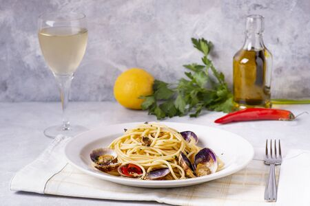in the foreground, on a textured gray background, fragrant plate of spaghetti with clams