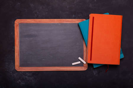 on a black structure background, with top view, a school blackboard with chalks and diary. Copy space