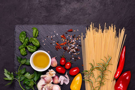 Italian food: on a slate stone, raw spaghetti, garlic, olive oil and numerous ingredients with aromatic herbs. View from above