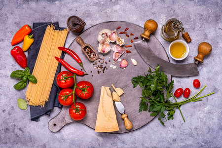 Italian food: on a gray wooden cutting board, raw spaghetti, aged cheese and numerous ingredients and aromatic herbs, a crescent knife. view from above