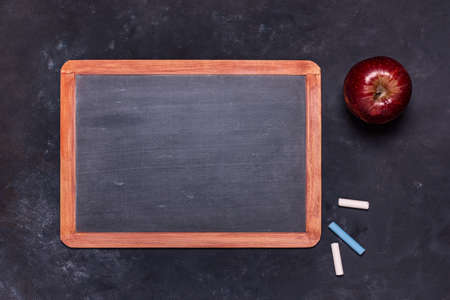 on a black structure background, with top view, a school blackboard with chalks and a red apple. Copy space