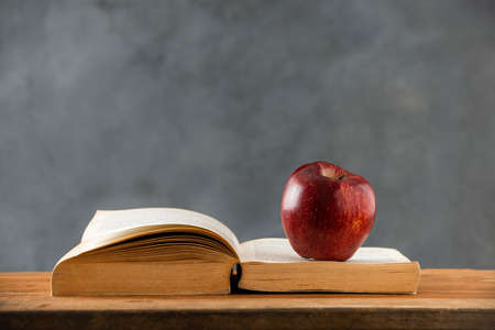 on the wooden table, an open book with a red apple on it. copy space Zdjęcie Seryjne