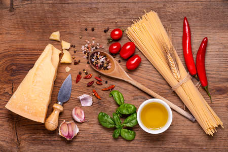 board, raw spaghetti, seasoned Grana Padano cheese, garlic, oil and numerous ingredients with aromatic herbs. View from above