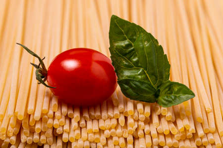 in the foreground: raw spaghetti, a cherry tomato and fresh basil leaves. Italian food concept.
