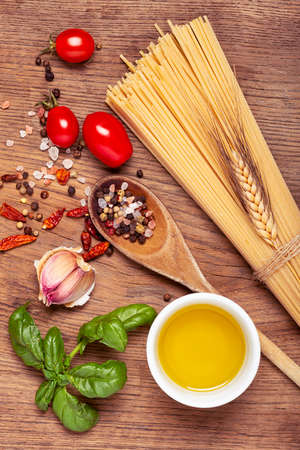 Italian food: raw spaghetti, garlic, olive oil and numerous ingredients with aromatic herbs on a raw wooden board. View from above