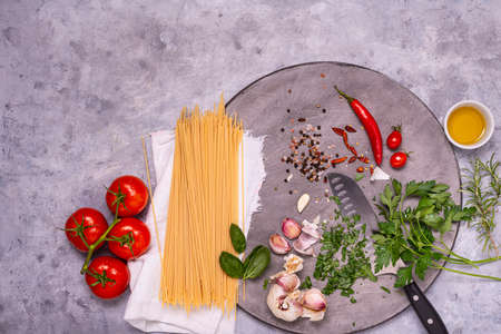 Italian food: on a gray wooden cutting board, raw spaghetti, garlic, olive oil, pepper, and numerous ingredients and herbs, top view Zdjęcie Seryjne