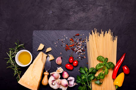 Italian food: on a slate stone, raw spaghetti, aged grana padano cheese, garlic, oil and numerous ingredients with aromatic herbs. View from above Zdjęcie Seryjne