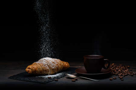 on the rustic wooden table and dark background, a steaming cup of coffee with croissants and cascade of powdered sugar. Still life