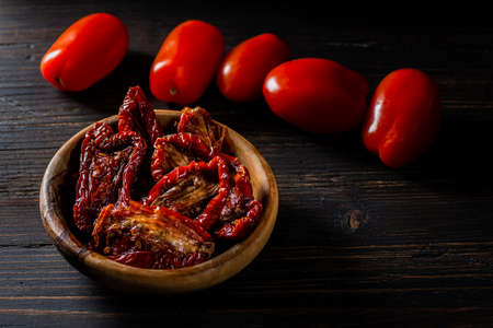 On the dark wooden table, a wooden bowl with dried tomatoes softened with olive oil. A few fresh tomatoes aside.