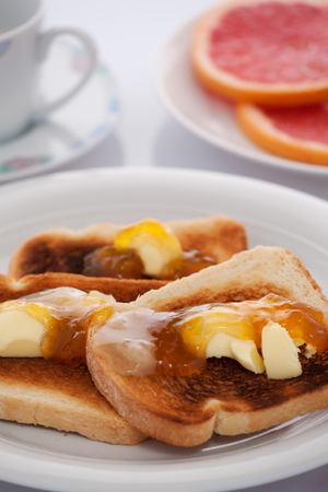 vetical: French toast and sliced orange on white tablecloth Foto de archivo