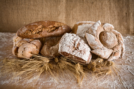 life loaf: Bread of various types with ears of wheat and jute background