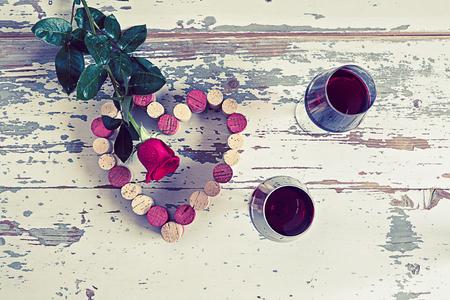 flor morada: Dos vasos de vino tinto, corchos y una rosa roja