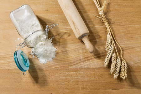 glass jar: Flour in glass jar on a table with rolling pin and sheaves of wheat from above