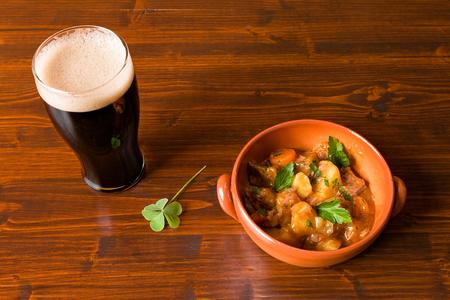 stout: Estofado irlandés tradicional en un tazón de café con una pinta de cerveza negra y un trébol en una mesa.