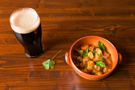 cerveza negra: Traditional Irish Stew on a brown bowl with a pint of stout beer and a shamrock on a table.