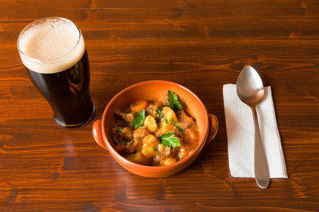 cerveza negra: Traditional Irish Stew on a brown bowl with a pint of stout beer and a spoon over a napkin on a table. Foto de archivo