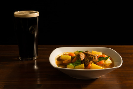 Traditional Irish Stew with a pint of beer on a table.