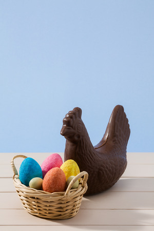 over white background: Easter chocolate chicken and colored eggs in a small basket over a white table with blue background