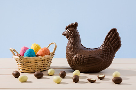 blue background: Easter chocolate eggs in a small basket and a hen with some small eggs over a white table and a blue background Stock Photo