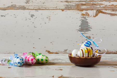 painted wood: Painted handmade easter eggs inside a wood bowl on wood background