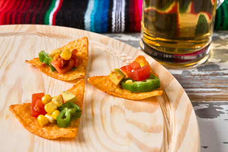 tex mex: Close up of nachos chips with vegetables and beer with a poncho on background