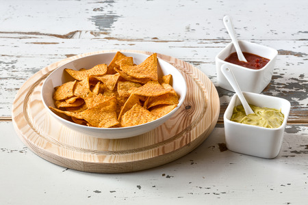 kilos: Nachos chips in a white bowl over a chopping board with sauces on a wood background Stock Photo
