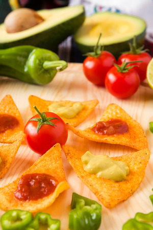 tex mex: Close up of nachos chips tomato pepper and avocado over a chopping board