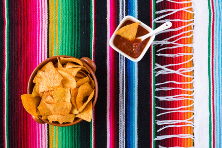 tex mex: Nachos chips and tomato sauce over a colored poncho seen from above Stock Photo