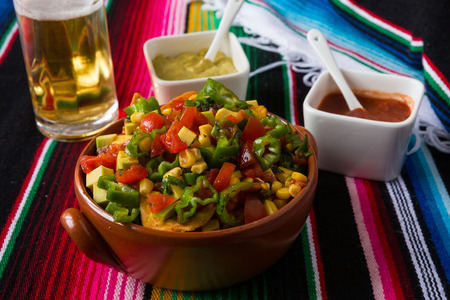 tex mex: Nachos salad hot sauces and beer over a colored poncho