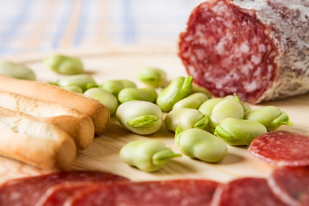 broad bean: Close up of broad bean and bread sticks with Italian salami over a chopping board