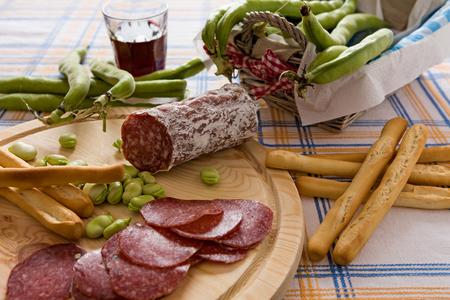 caloric: Italian salami broad bean and bread sticks over a chopping board
