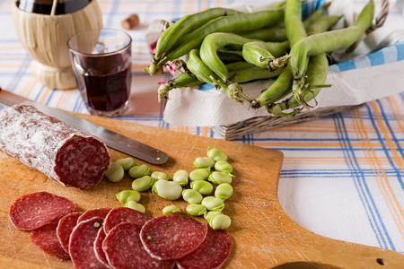broad bean: Chopping board with salami broad bean and a glass of red wine