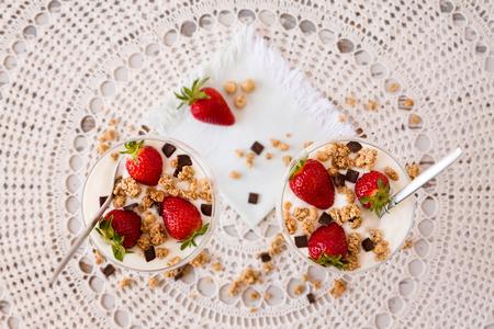 yogurt natural: Fresas cereales y copos de chocolate en el interior del yogur natural visto desde arriba