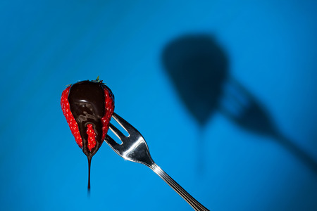 liquid chocolate: Close up of a strawberry suspended from a fork and its shadow on background with liquid chocolate above